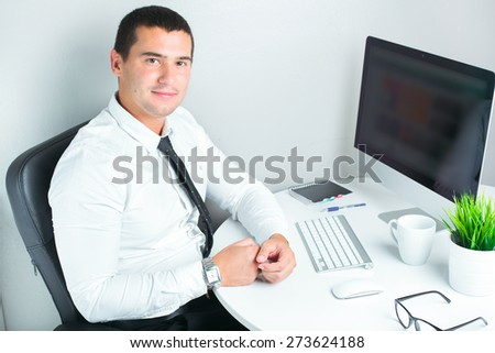 portrait of a successful businessman at office working on computer - stock photo