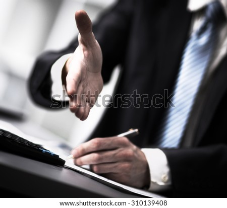 Portrait of a successful businessman giving a hand - stock photo