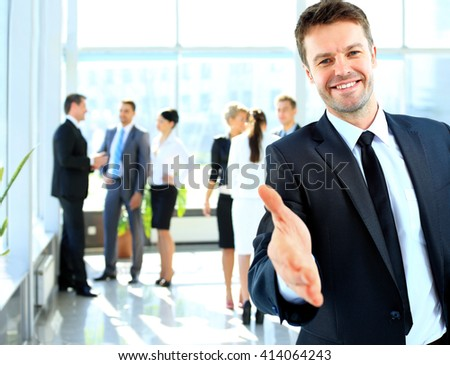 Portrait of a successful businessman giving a hand