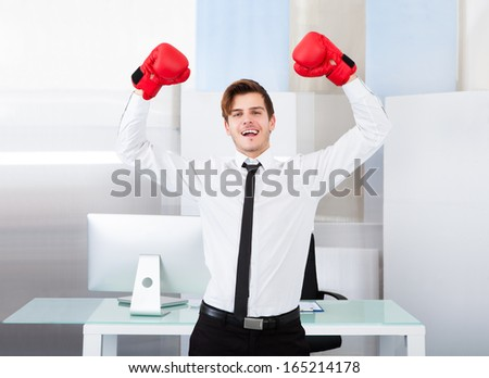 Portrait Of A Successful Businessman Wearing Red Boxing Gloves In Office - stock photo