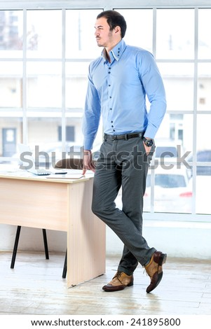Portrait of a successful businessman. Young businessman in business attire is standing at the desk in the office and looking to the side. - stock photo