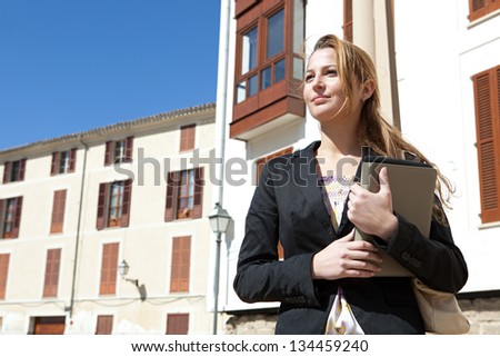 Portrait of a successful businesswoman holding a digital tablet pad and a folder while proudly standing near classic city buildings.