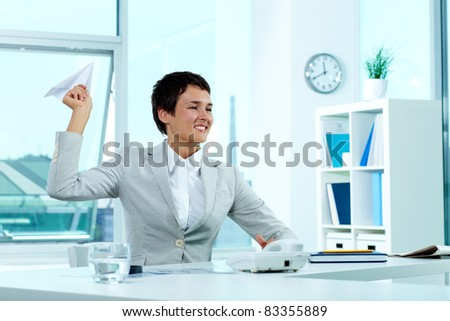 Portrait of a successful employer at workplace holding paper plane
