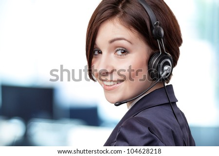 Portrait of a successful female call centre employee wearing a headset - stock photo