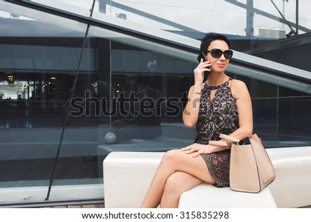 Portrait of a successful female entrepreneur dressed in elegant clothes speaking on her phone while sitting near office building, charming woman having mobile phone conversation in urban setting - stock photo