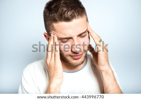 Portrait of a successful man has a headache, isolated on a gray background
