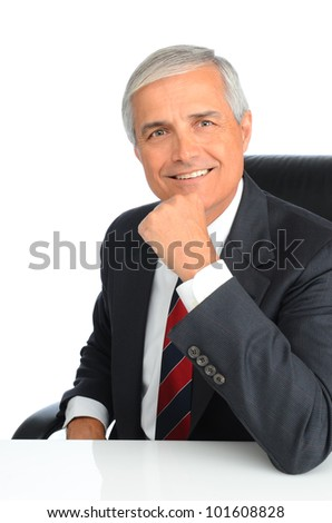 Portrait of a successful mature businessman seated at a desk with his hand on his chin. Man is smiling. Vertical format over white background. - stock photo