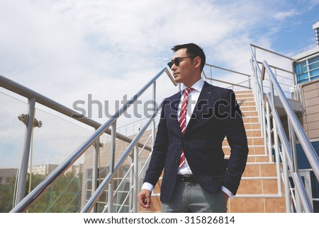 Portrait of a successful smart asian men dressed in elegant clothes standing on the street while having cigarette during work break, young confident businessman in formal wear resting after hard day - stock photo