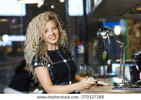 Portrait of a successful smiling woman, the owner of the restaurant with a smartphone - stock photo
