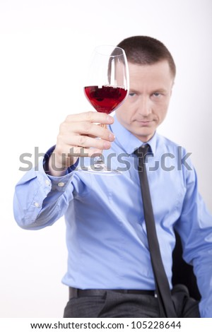 Portrait of a successful young business man holding glass of wine.