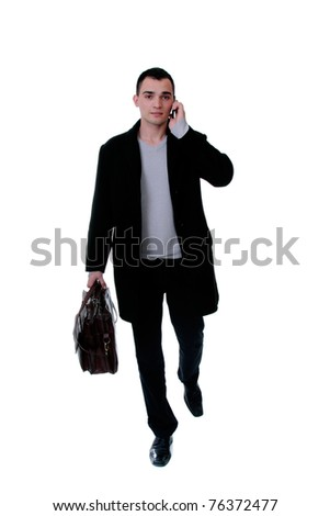 Portrait of a successful young business man on the phone carrying a suitcase on white background - stock photo