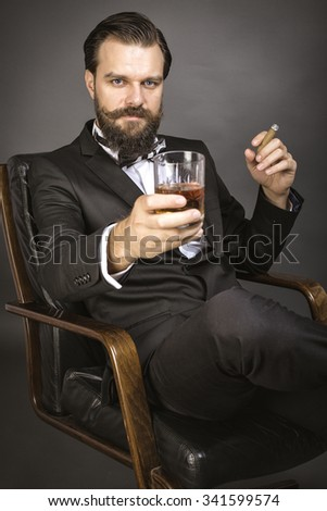 Portrait of a successful young  man with retro look sitting in an armchair and holding a glass of whiskey over gray background - stock photo