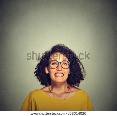 Portrait of a super excited happy funky girl in glasses looking up isolated on grey wall background - stock photo