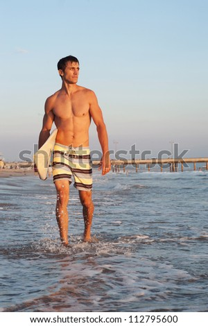 portrait of a surfer on the beach with surfboard - stock photo