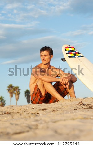 portrait of a surfer sitting on the beach with surfboard - stock photo