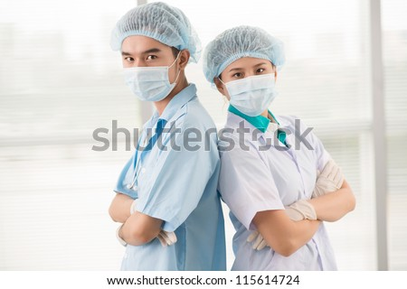Portrait of a surgical team standing back to back to provide backup - stock photo