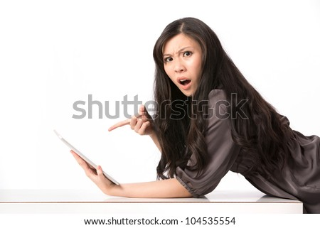 Portrait of a surprised Asian woman pointing at her touch screen tablet. - stock photo