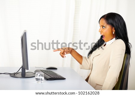 Portrait of a surprised business lady pointing the computer screen - stock photo