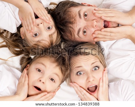 Portrait of a surprised family having fun together lying on a bed at home - top view - stock photo