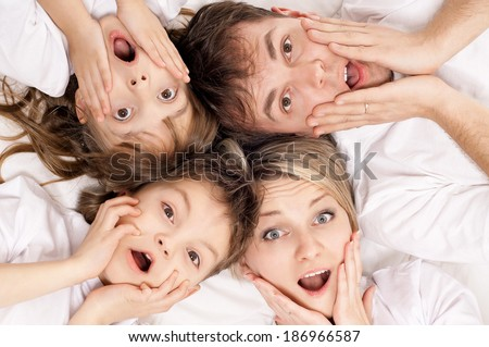 Portrait of a surprised family having fun together lying on a bed at home - top view