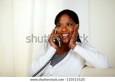 Portrait of a surprised female smiling and conversing on phone at soft colors composition