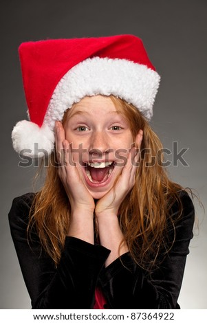 Portrait of a surprised girl wearing a Santa hat.