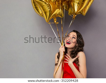 Portrait of a surprised happy woman in red dress holding balloons over gray background - stock photo