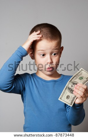 Portrait of a surprised little boy holding a dollars - stock photo