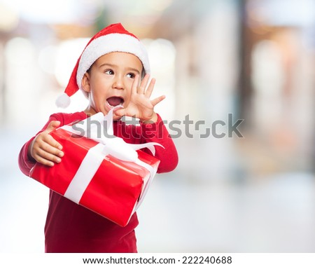 portrait of a surprised little boy with his gift - stock photo