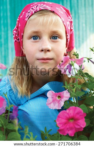 Portrait of a surprised little girl sitting in the garden on a background of pink flowers - stock photo