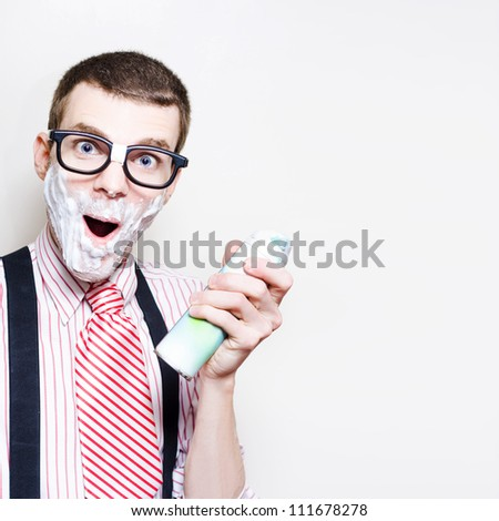 Portrait Of A Surprised Man Wearing Nerd Glasses Holding Shaving Cream With Foam Beard In A Depiction Of Sensitive Skin, Studio Background