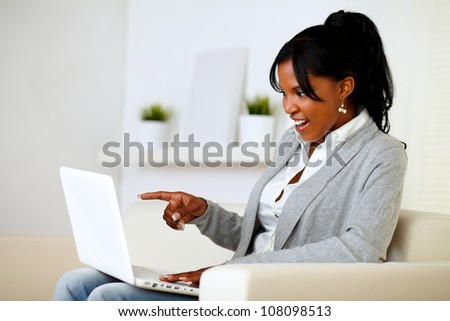 Portrait of a surprised woman pointing to laptop screen while is sitting on sofa at home