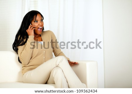 Portrait of a surprised woman sitting at home on sofa while listening to good news for the mobile - stock photo
