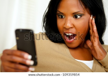 Portrait of a surprised young woman reading a message on cellphone - stock photo