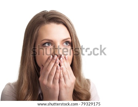 Portrait of a surprised young woman with hands over her mouth laughing against white background - stock photo