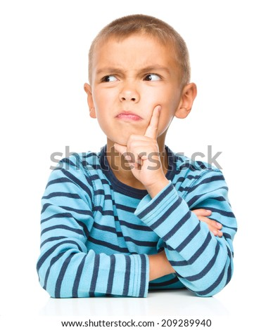 Portrait of a suspicious little boy touching his cheek with index finger, isolated over white - stock photo