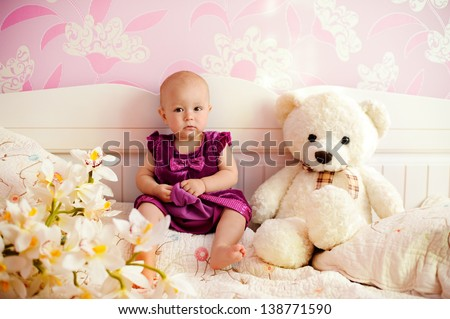 Portrait of a sweet baby girl with her bear and flower indoor