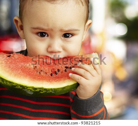 portrait of a sweet kid eating a watermelon slice against a carousel background
