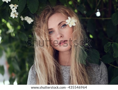 portrait of a sweet young girl close-up in the city of jasmine flowers in summer