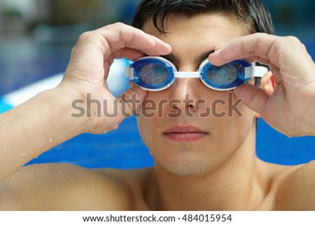 Portrait of a swimmer putting on his goggles in the swimming pool