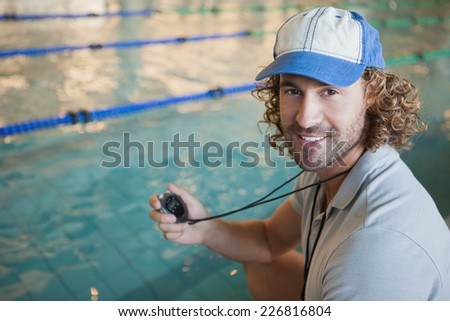 Portrait of a swimming coach by the pool smiling at leisure center - stock photo