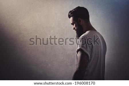 Portrait of a tattooed bearded man - stock photo