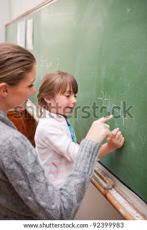 Portrait of a teacher and a pupil making an addition on a blackboard - stock photo