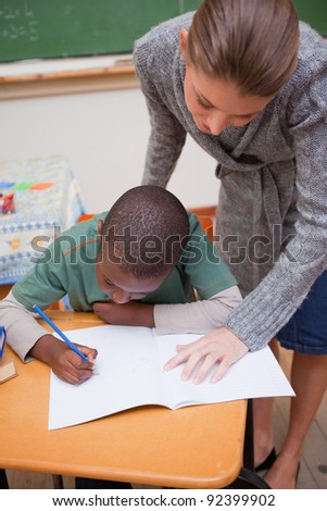 Portrait of a teacher explaining something to a focused schoolboy in a classroom - stock photo