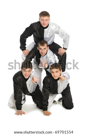 Portrait of a team of young break dancers with elements of dance in stylish uniforms. Two guys show the index finger at the camera.
