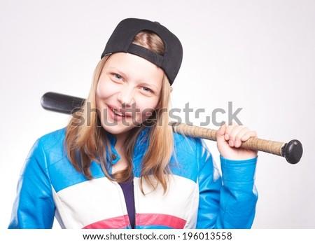 Portrait of a teen girl with bat, studio shot - stock photo