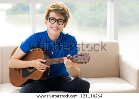 Portrait of a teen guitar player smiling at the camera - stock photo