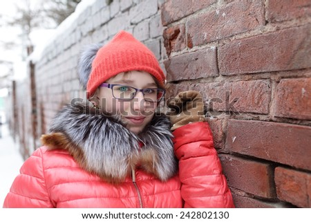 Portrait of a teen next to brick wall in winter - stock photo