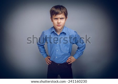 portrait of a teenage boy frowning brown hair of European appearance on a gray background cross process - stock photo