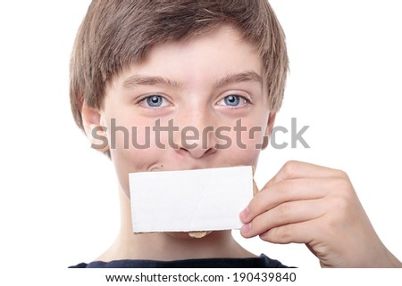 portrait of a teenage boy holding a white piece of cardboard in front of one eye.